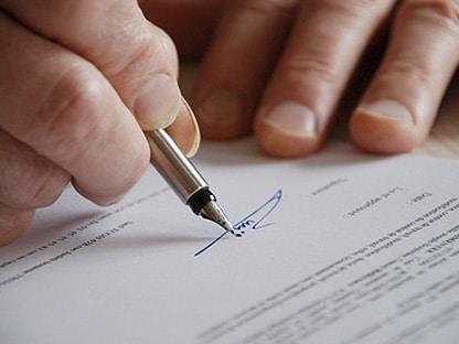 firma de una persona en un documento de derogación de normativa de viñedos