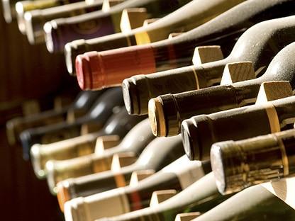 grupo de botellas de vino colocadas tumbadas en un botellero de la bodega
