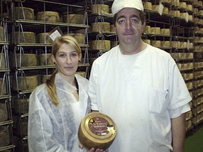 personal en una quesería posando con un queso certificado con la marca de garantía queso castellano