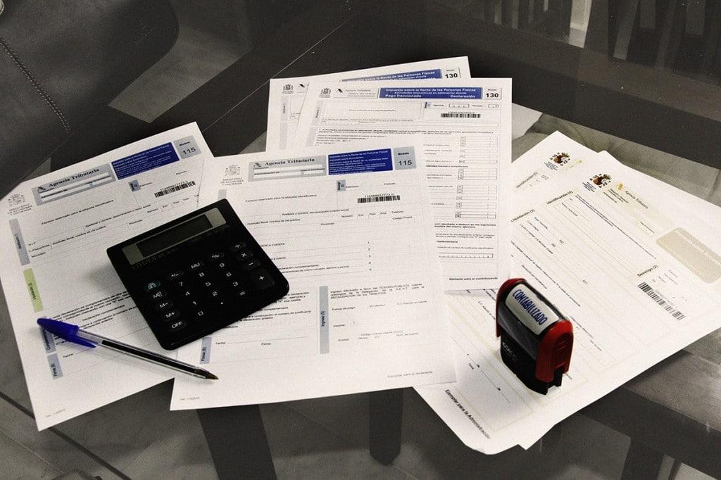 mesa sobre la que aparecen varios impuestos especiales sobre el vino, calculadoras y bolígrafos