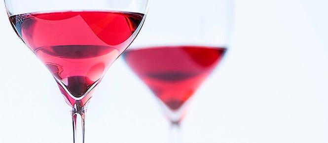 dos copas de vino rosado sobre una iluminación especial