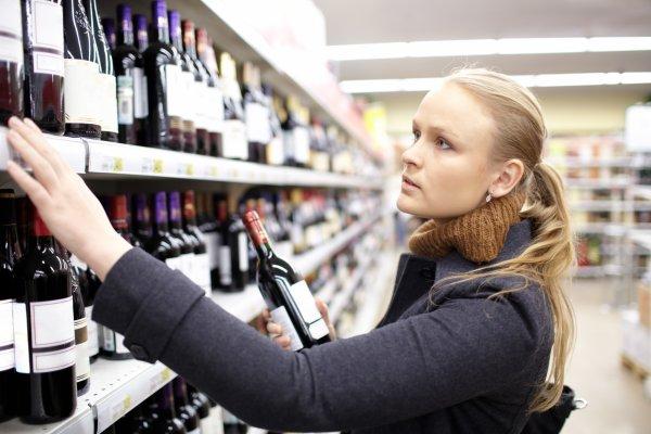 mujer examinando en el lineal de venta varios etiquetados de vino