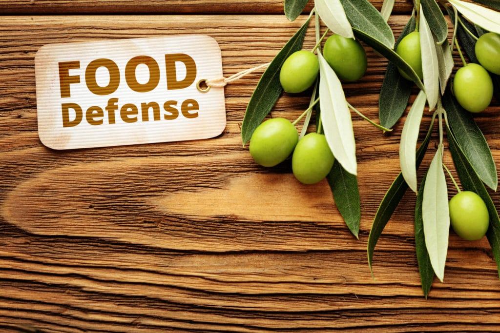 mesa sobre la que hay una rama de olivo con varias aceitunas y un cartel que pone food defense