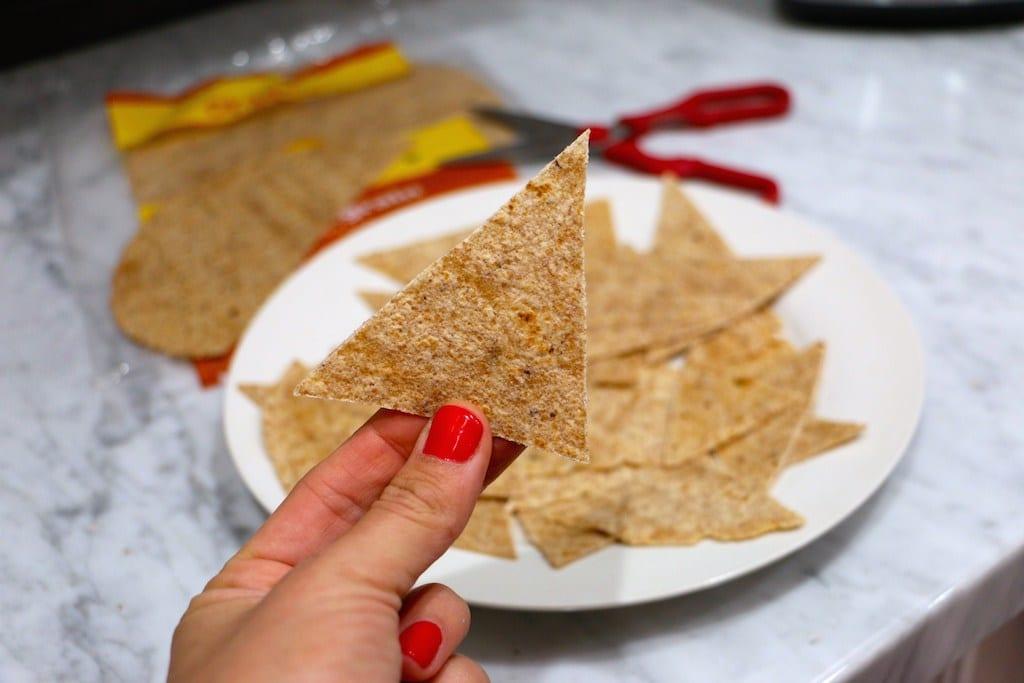 mano de una mujer sosteniendo un nacho de tortilla sobre un fondo en el que se ven más nachos