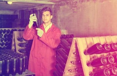 enólogo en una bodega llena de botellas de vino midiendo valores